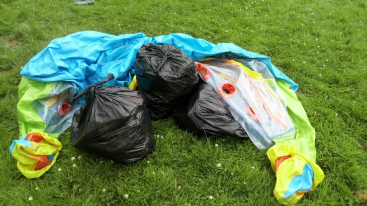 pile of bin bags with deflated children's paddling pool placed on grass