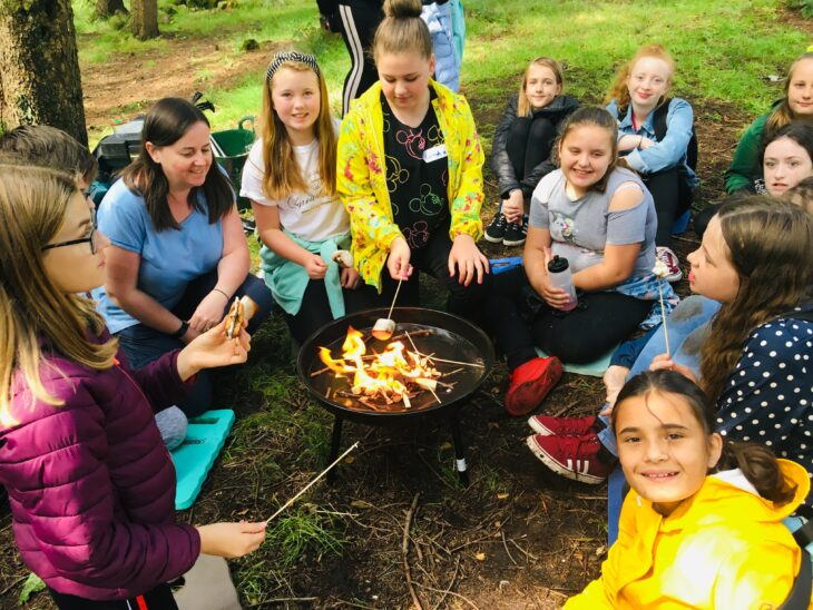 Group of girls sitting round campfire toasting marshmallows