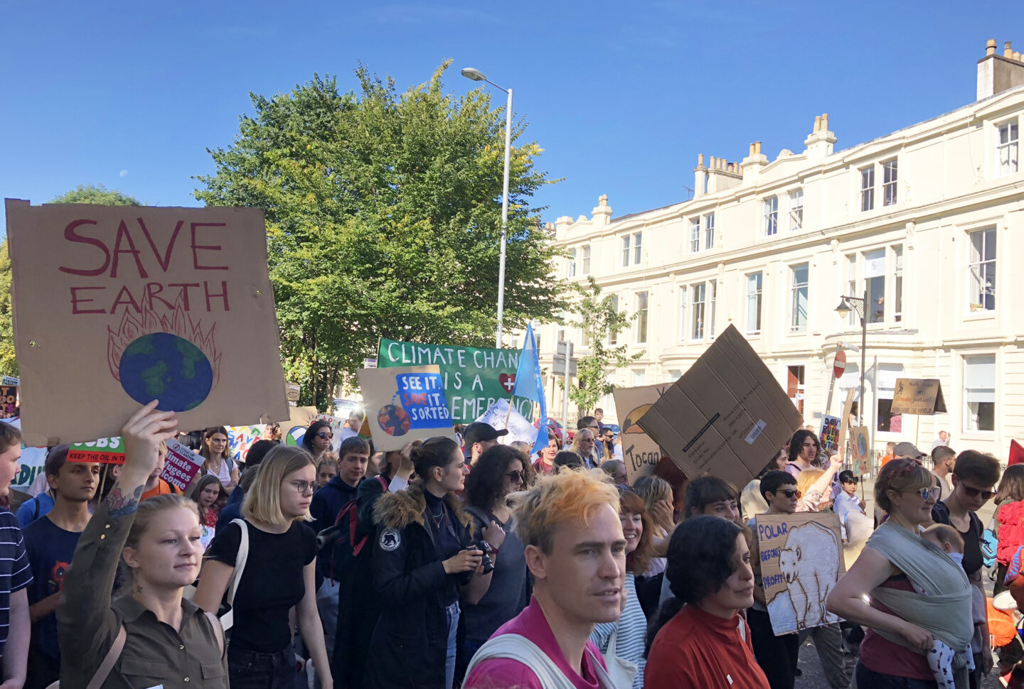 Climate protesters marching through Glasgow street holding cardboard signs
